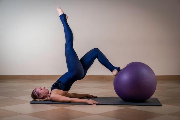 Atlética garota deitada em uma esteira de ginástica fazendo alongamento com uma perna na bola