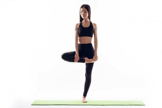 Atlética garota está de pé em uma perna.