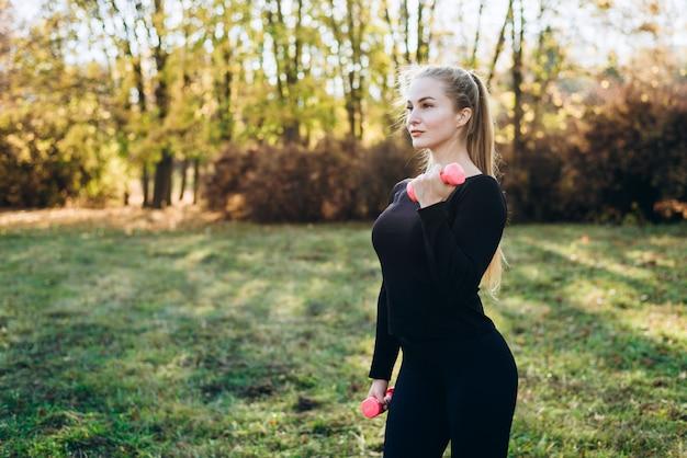 Atlética garota fazendo aptidão ao ar livre com halteres, vista lateral.