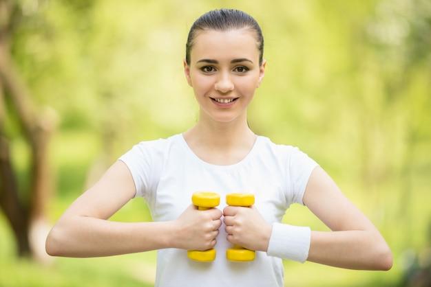 Atlética garota fazendo exercícios com halteres ao ar livre.