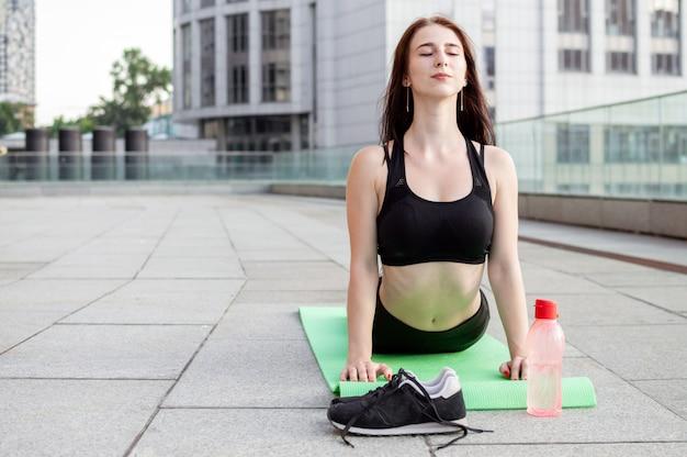 Atlética garota fazendo yoga pela manhã na rua, ela faz alongamento na cidade, mulher fitness treina no tapete