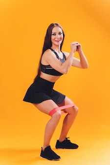 Atlética garota realiza exercícios usando uma banda de resistência. foto de jovem em fundo. força e motivação.