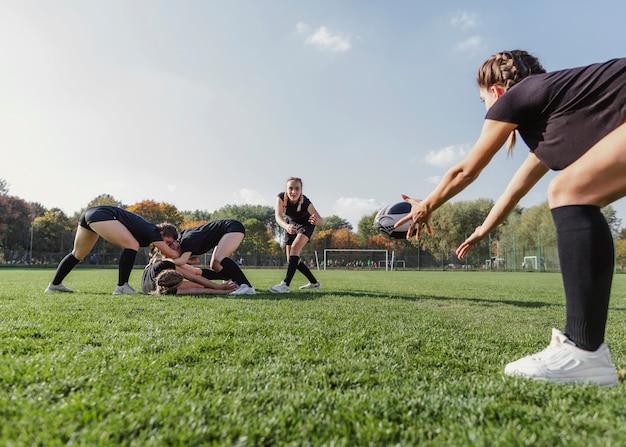 Atlética garota tentando pegar uma bola de rugby