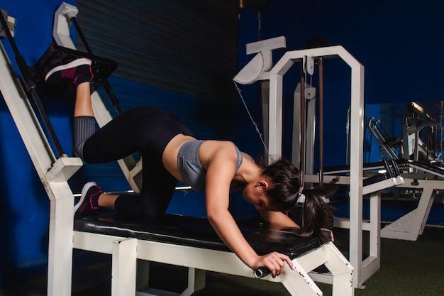 Atlética garota treinando glúteos com uma máquina na academia.
