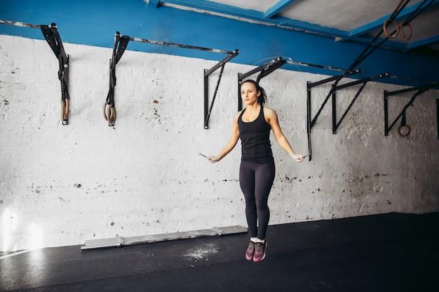 Atlética garota usando cordas de pular para o treino em uma academia