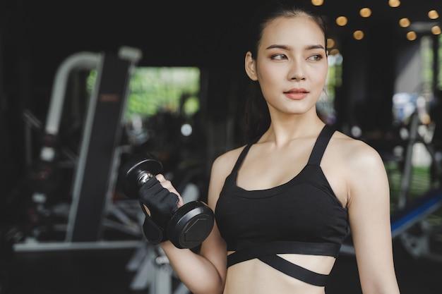 Atlética jovem asiática corpo muito magro mulher exercício com halteres no ginásio de fitness com máquina, fisiculturista, estilo de vida saudável, exercício fitness, treino e conceito de treinamento de esporte