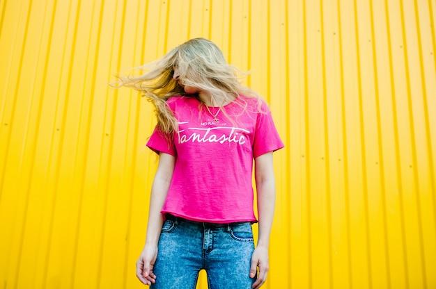 Atlética jovem bonita com longos cabelos loiros na camisa rosa e calça jeans azul. posando e sorrindo para a parede da garagem em yellowwall. faz saltos, voando.