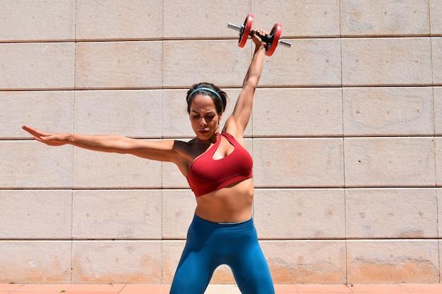 Atlética jovem caucasiana malhando ao ar livre e alongamento