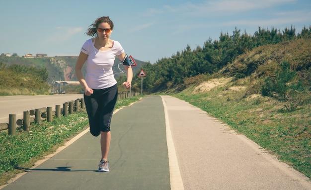 Atlética jovem com fones de ouvido, ouvindo música de seu smartphone enquanto corre em uma pista ao ar livre. conceito moderno de estilo de vida saudável.