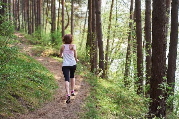 Atlética jovem de tênis rosa correr na floresta de primavera