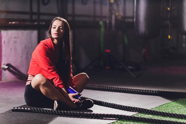 Atlética jovem fazendo alguns exercícios com uma corda ao ar livre.