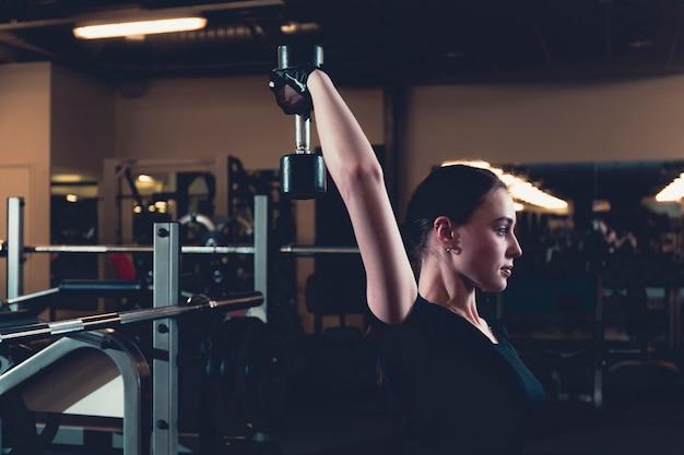 Atlética jovem fazendo tríceps exercício com halteres no centro de fitness
