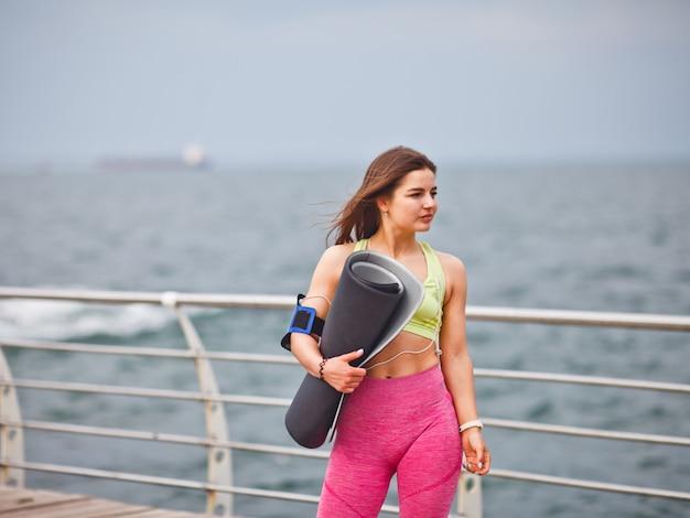Atlética jovem no sportwear tem tapete de ioga na mão e posando ao ar livre na praia