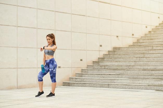 Atlética mulher asiática em pé ao ar livre com garrafa de água e olhando para o relógio de pulso