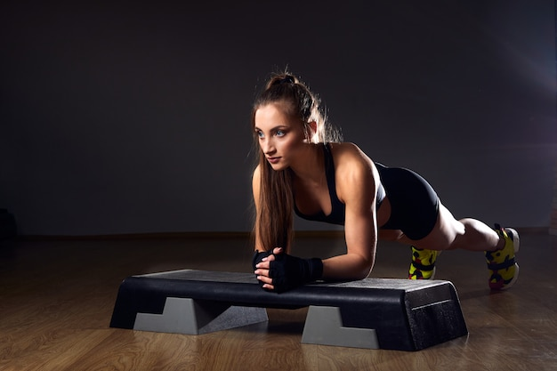 Atlética mulher bonita faz exercícios - posição de prancha. treino cross fitness e musculação com etapa aeróbica.