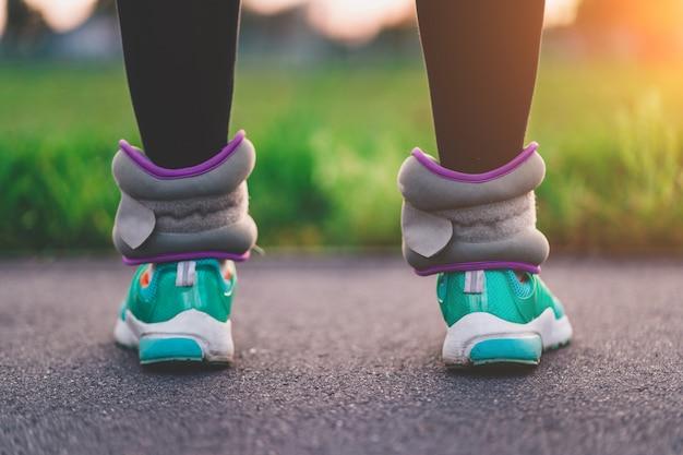 Atlética mulher caminha com pesos esportivos para fortalecer os músculos e resistência durante o treino ao ar livre. estilo de vida saudável e esportivo.