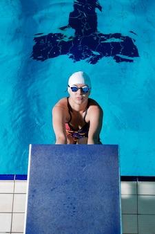 Atlética mulher com chapéu de natação e óculos pronta para começar a corrida de natação na piscina