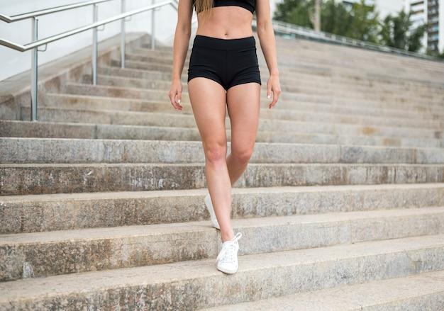 Atlética mulher correndo pelas escadas