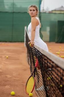Atlética mulher em pé perto da rede na quadra com a raquete nas mãos.