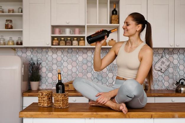 Atlética mulher em um agasalho em uma cozinha leve bebe vinho tinto de uma garrafa depois de praticar esportes.
