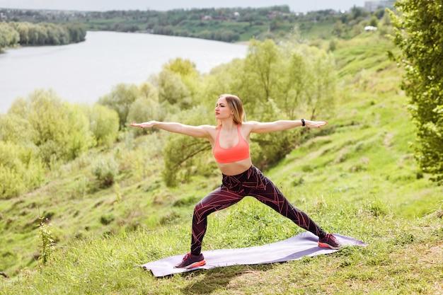 Atlética mulher está praticando ioga, em pé no guerreiro dois exercício
