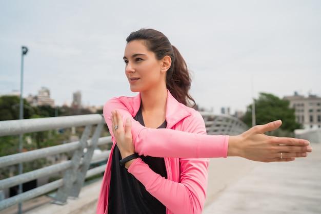 Atlética mulher esticando as pernas antes do exercício.