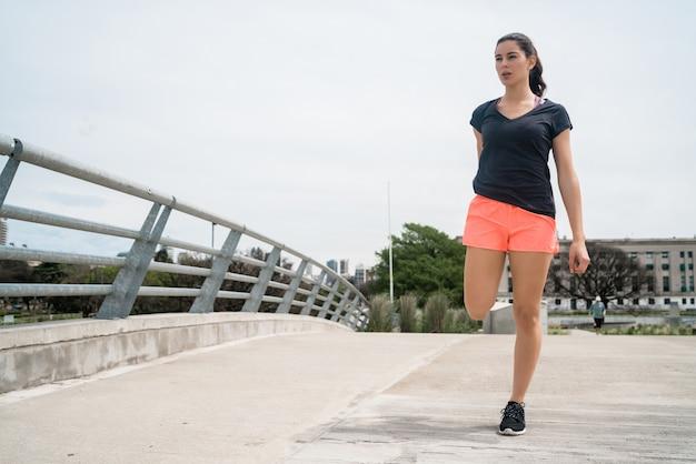 Atlética mulher esticando as pernas antes do exercício