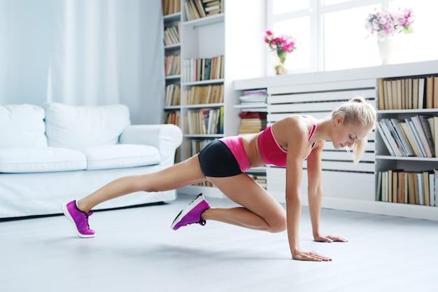 Atlética mulher exercitando em casa, treino