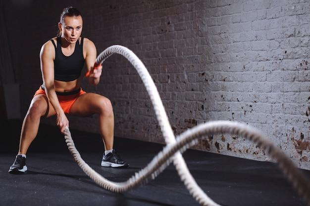 Atlética mulher fazendo exercícios de corda de batalha no ginásio