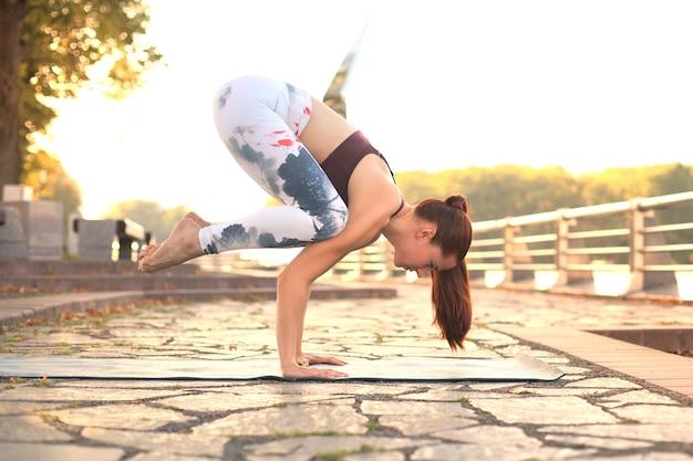Atlética mulher forte praticando difícil pose de ioga ao ar livre.