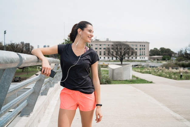 Atlética mulher ouvindo música em um intervalo de treinamento.