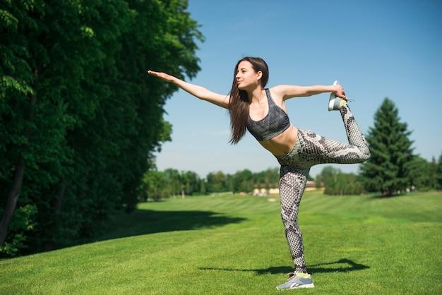 Atlética mulher praticando ioga ao ar livre