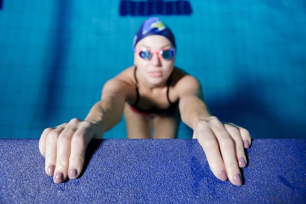 Atlética mulher pronta para começar a natação corrida na piscina. foco nas mãos