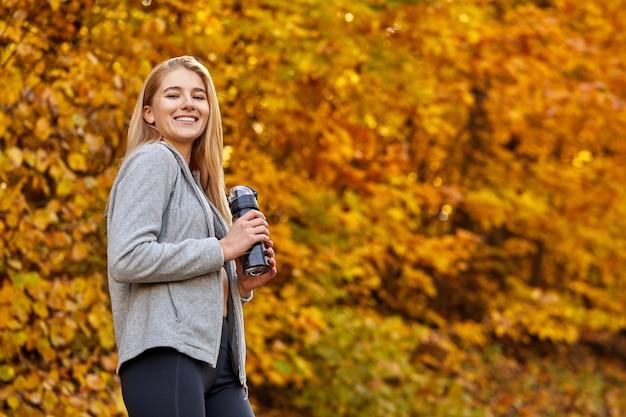 Atlética mulher segurando uma garrafa de água limpa na floresta de outono