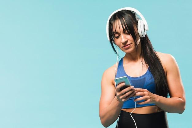 Atlética mulher vestida de academia, ouvindo música em fones de ouvido