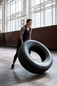 Atlética tatuada mulher caucasiana em roupa esportiva preta jogando pneu pesado durante o treinamento cruzado em uma sala de esportes