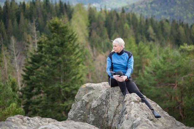 Atlética velha mulher sentada no topo da rocha