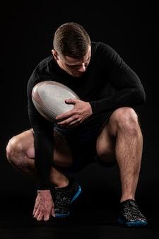 Atlético bonito jogador de rúgbi segurando a bola enquanto posa
