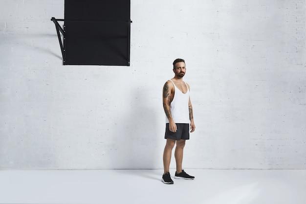 Atlético brutal e tatuado jovem em t-shirt do tanque em branco liso em pé perto da barra de pull-up em frente a parede de tijolos de grunge no ginásio branco.