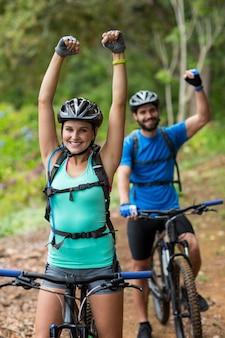 Atlético casal dançando com bicicleta de montanha na floresta