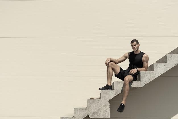 Atlético desportista despreocupado posando enquanto está sentado e sorrindo na escada
