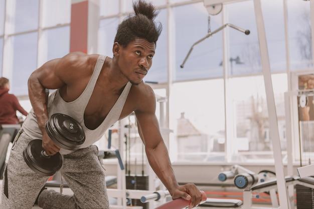 Atlético homem africano malhando com halteres na academia