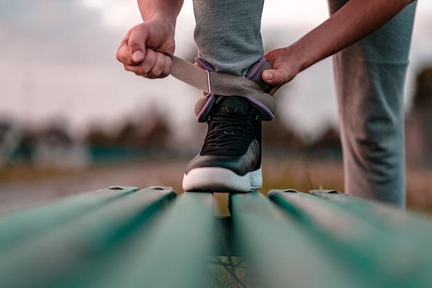 Atlético homem coloca pesos de esportes para caminhar durante o treino ao ar livre. estilo de vida saudável e esportivo.