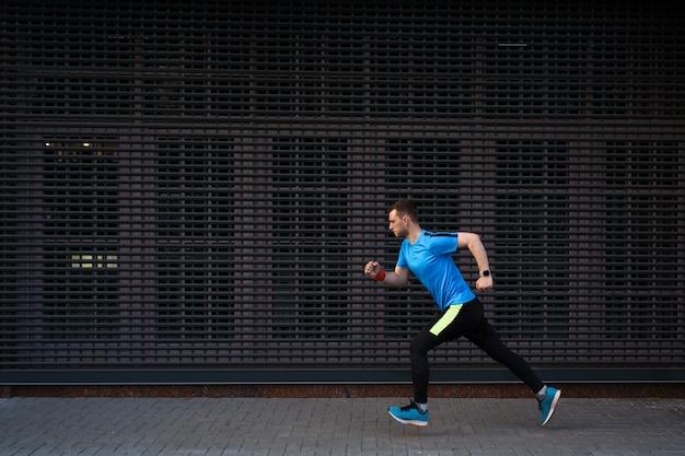 Atlético homem correndo na rua urbana contra fundo cinza
