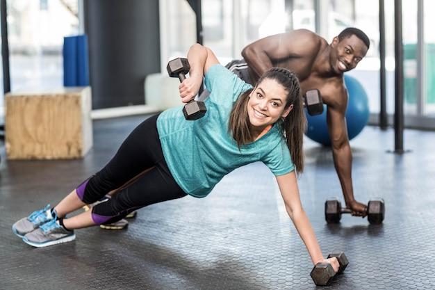 Atlético homem e mulher malhando na academia crossfit