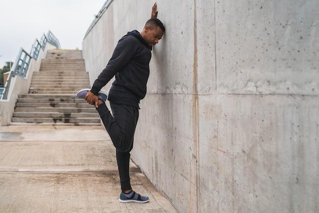Atlético homem esticando as pernas antes do exercício.