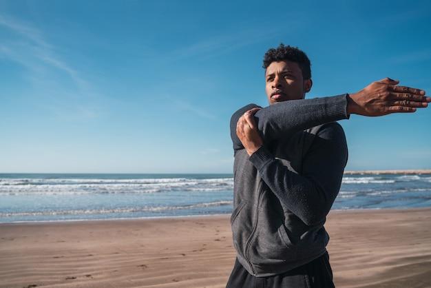 Atlético homem esticando os braços antes do exercício