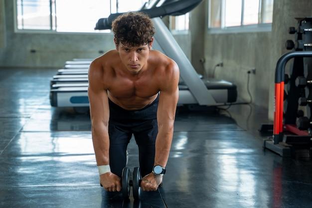 Atlético homem exercitar com rolo de fitness no clube de ginástica