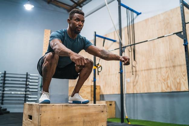 Atlético homem fazendo exercício de salto de caixa.