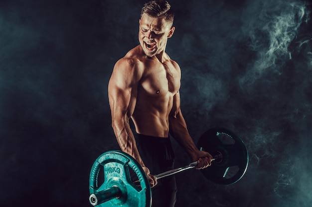 Atlético homem fazendo exercícios com halteres no bíceps. foto de homem forte com torso nu na parede escura. força e motivação.